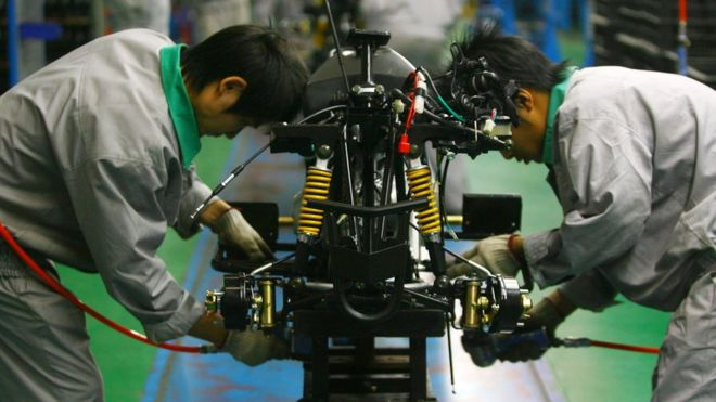 Workers labour on the production line of an all-terrain vehicle at the Chongqing Longcin Motorcycle Company on November 6, 2007 in Chongqing Municipality, China.