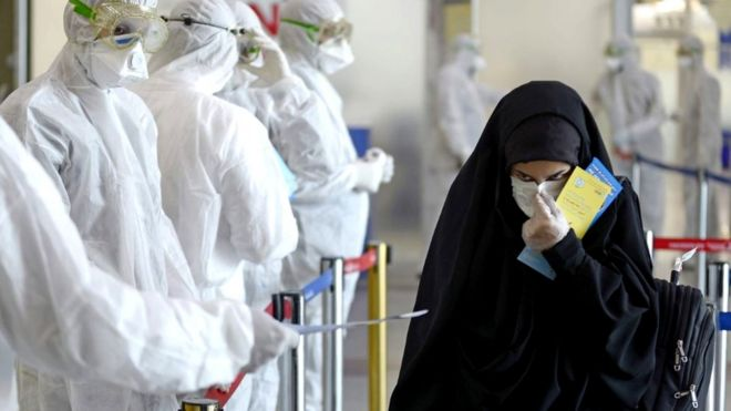 Medical staff in protective gear distribute leaflets to Iraqi passengers returning from Iran, 5 March 2020