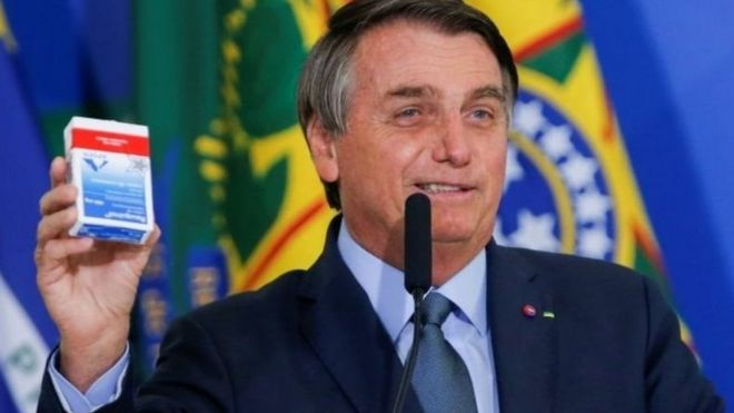 Jair Bolsonaro sorri e segura embalagem de hidroxicloroquina