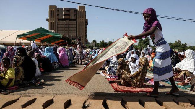 Une jeune fille apprêtant son tapis de prière au premier jour de la fête de l'Aïd à Ouagadougou à la place de la nation.