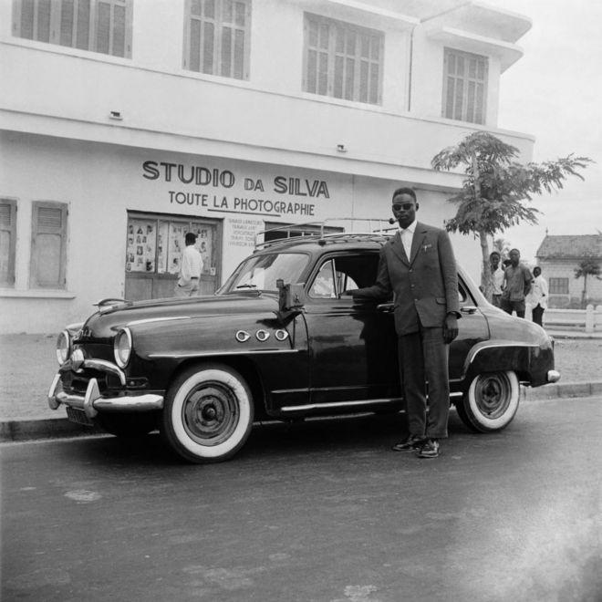 Un chauffeur vêtu d'une tenue élégante pose à côté de son véhicule, devant le studio de Roger DaSilva.