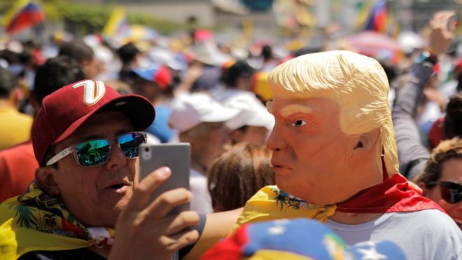 A man wearing a mask caricaturing US President Donald Trump poses for a selfie during a rally against Venezuelan President Nicolas Maduro's government in Caracas, February 2, 2019