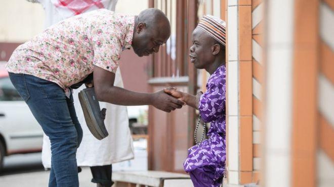 Deux musulmans se saluent après la prière de l'Aïd devant une mosquée à Libreville au Gabon dimanche.