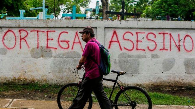 """Un hombre camina delante de u muro que dice """"Ortega asesino"""""""