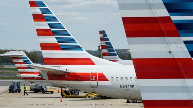 A member of a ground crew walks past American Airlines planes parked at the gate during the coronavirus disease (COVID-19) outbreak at Ronald Reagan National Airport in Washington, U.S., April 5, 2020.