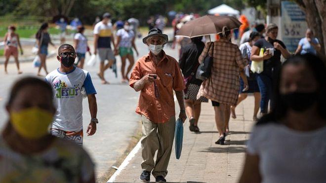 Pessoas caminham por rua de cidade brasileira