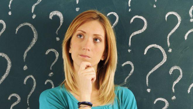 Una mujer pensando con signos de interrogación alrededor