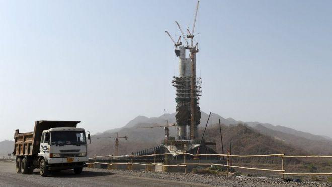 La estatua junto a un camión de construcción.
