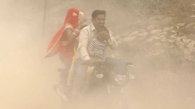 Indian family on motorbike in heavily polluted air