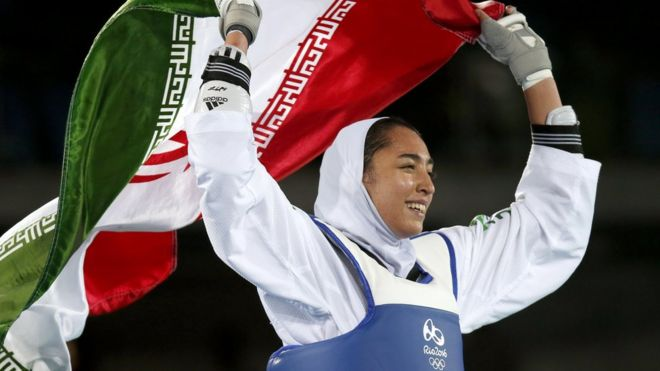 Kimia Alizadeh of Iran celebrates with the national flag after winning the women's -57kg bronze medal bout of the Rio 2016 Olympic Games Taekwondo event