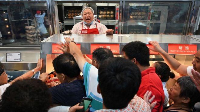 Los clientes se agolpan en la sección de pollos asados de Costco en Shanghái, China.