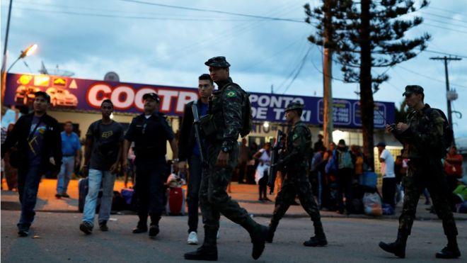 Солдаты армии патрулируют на улице рядом с людьми из Венесуэлы после проверки их паспортов или удостоверений личности на пограничном пункте Пакарайма, штат Рорайма