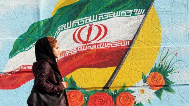 Mulher com véu passa em frente a pintura na parede da bandeira do Irã