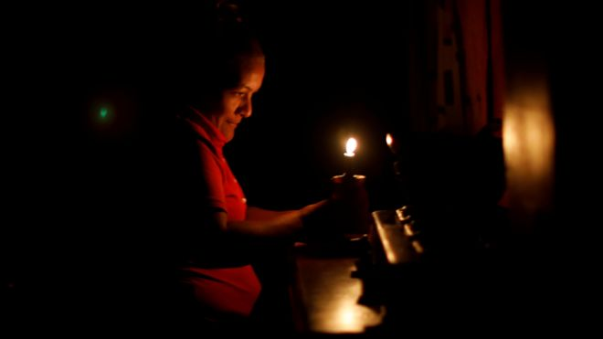 Una mujer se ilumina con una vela en Venezuela.