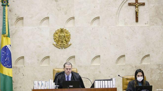 Dias Toffoli sentado no centro do plenário do STF, ao lado de assistente com máscara