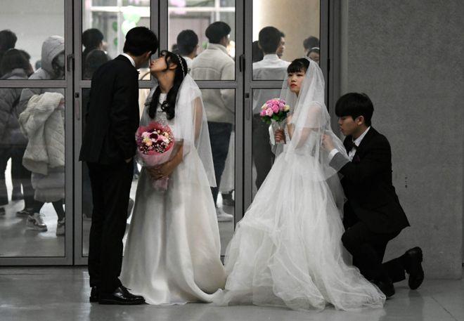 الأزواج وهم يستعدون لعروضهم في حفل زفاف جماعي تنظمه كنيسة التوحيد في غابيونغ