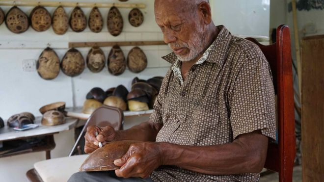 Faustulus Frederick decorating a calabash gourd