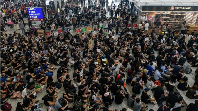 Hong Kong pro-democracy protesters (bottom) block access to the departure gates