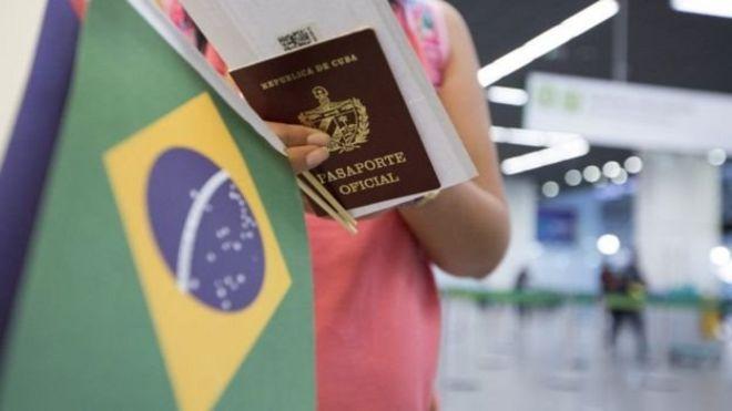 Pessoa com passaporte cubano e bandeira do Brasil