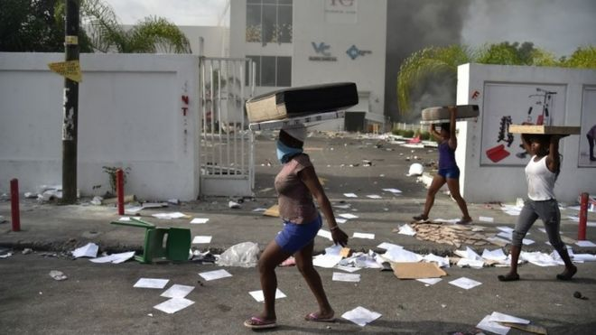 In this file photo taken on July 7, 2018 People carry loot from a shop in the commune of Petion Ville during protest against the increase in fuel prices, in Port-au-Prince.