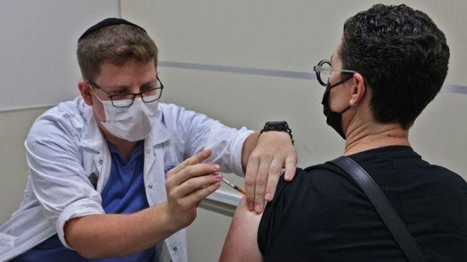 Trabajador de la salud vacunando una persona en Israel