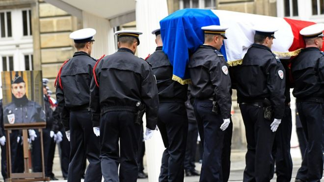 French police officers carry the flag-draped casket at the end of a ceremony honouring the policeman killed (pictured L) by a jihadist in an attack on the Champs Elysees, on 25 April 2017 at the Paris prefecture building