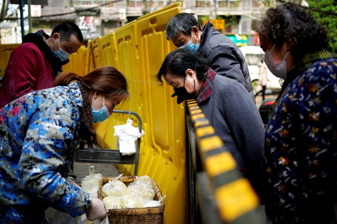 Residents wearing face masks pay for noodles