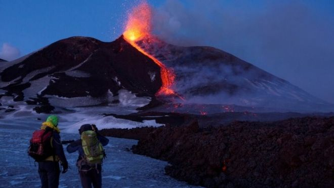 "Volcano guides stand in front of Italy""s Mount Etna, Europe""s tallest and most active volcano"