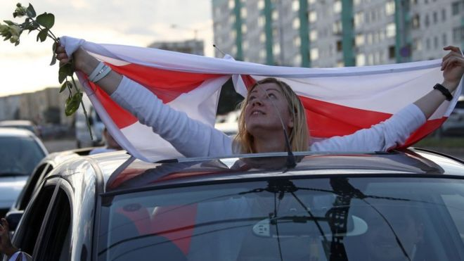 A car passenger displays a Belarusian flag