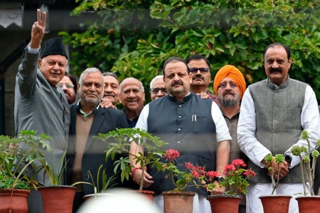 Former Jammu and Kashmir chief minister and leader of regional National Conference (NC) Farooq Abdullah (L) along with party colleagues gestures at his residence in Srinagar on October 6, 2019.
