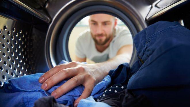 Homem coloca roupa em máqiuona de lavar