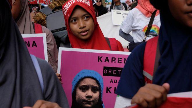 Joven con cartel de Greta Thunberg