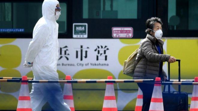 A passenger leaves the Diamond Princess cruise ship - in quarantine due to fears of the new Covid-19 coronavirus - at the Daikoku Pier Cruise Terminal in Yokohama, 19 February 2020