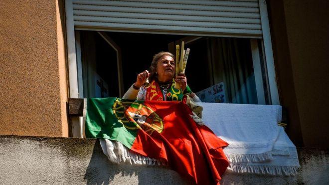 Mujer con la bandera de Portugal en la ventana.