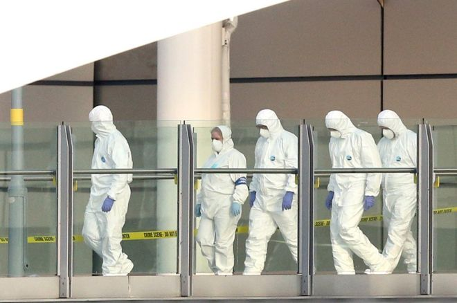 Police forensic officers leave the Manchester Arena as they investigate the scene of an explosion on May 23, 2017 in Manchester, England.