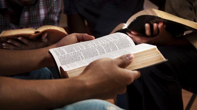Close nas mãos de pessoas segurando Bíblias em uma roda de conversa