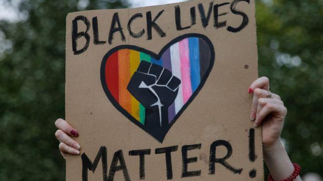 """متظاهرة ترفع لافتة مكتوب عليها """"حياة السود مهمة"""""""