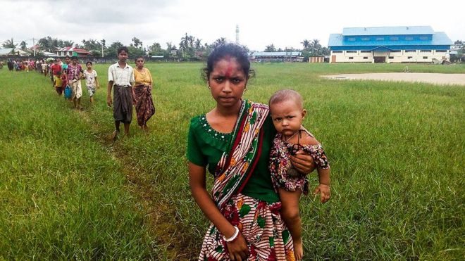 A woman holds a child in her arms as she arrives at the Yathae Taung township in Rakhine, Myanmar, after fleeing from violence in her village, 26 August