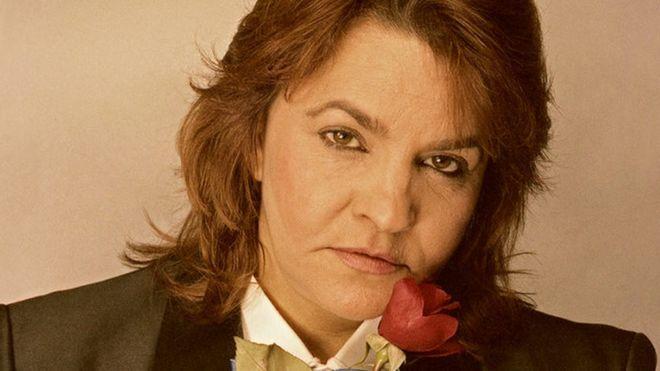 Cassandra Rios posa para foto segurando uma rosa e encarando a câmera