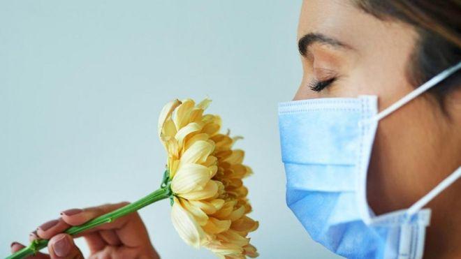 Mujer huele flor.