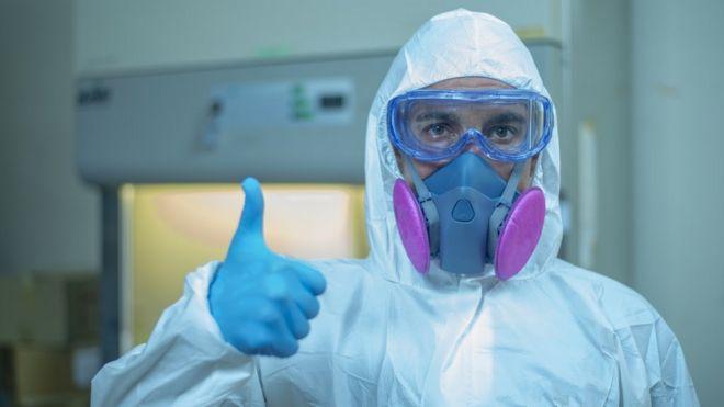 Una persona vestida con un traje de protección personal y con una máscara, con el pulgar arriba.
