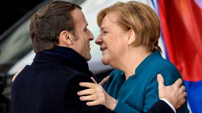 Эммануэль Макрон (слева) в темном костюме обнимает Ангелу Меркель (справа) в голубом пиджаке