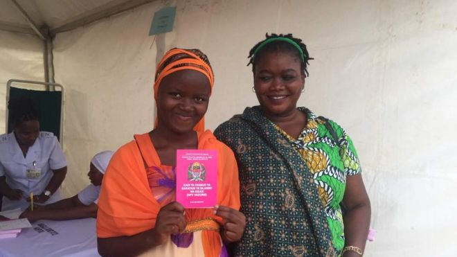 A girl who has been immunised poses with her vaccination booklet