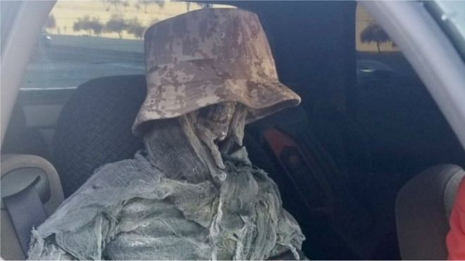 A fake skeleton in a camouflage bucket hat sits in the front of a vehicle in a handout image by the Arizona Department of Public Safety