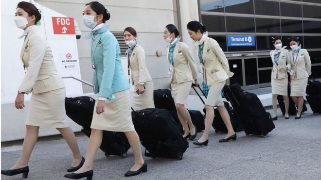 A flight crew from Korean Air, many wearing protective masks, depart the international terminal after arriving at Los Angeles International Airport (LAX) .