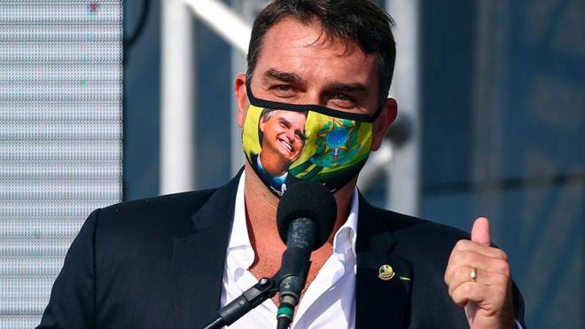 Flávio Bolsonaro com máscara com foto de Jair Bolsonaro