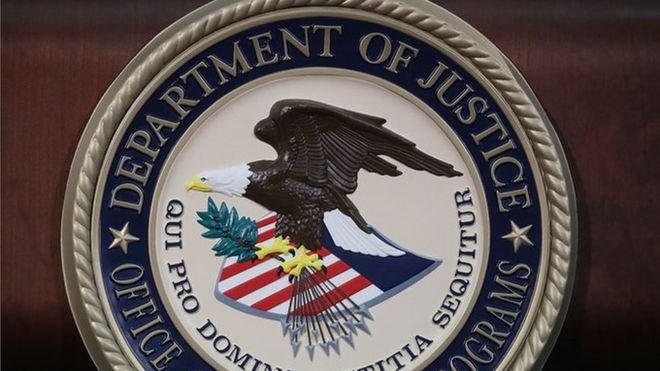 The US Department of Justice seal is seen on a lectern.