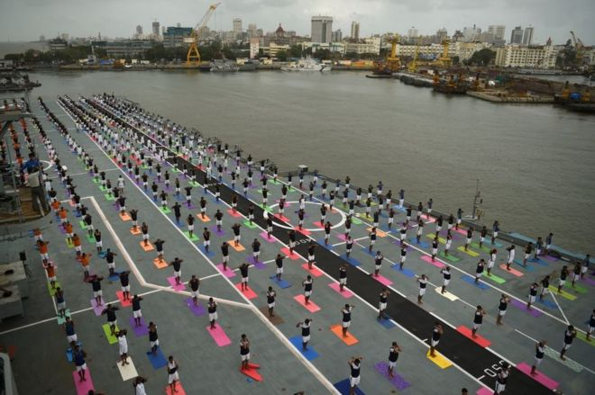 Indian Armed Forces personnel take part in a yoga sesssion to mark International Yoga Day on the Indian Navy aircraft carrier INS Viraat anchored at the Mumbai harbour on June 21, 2017