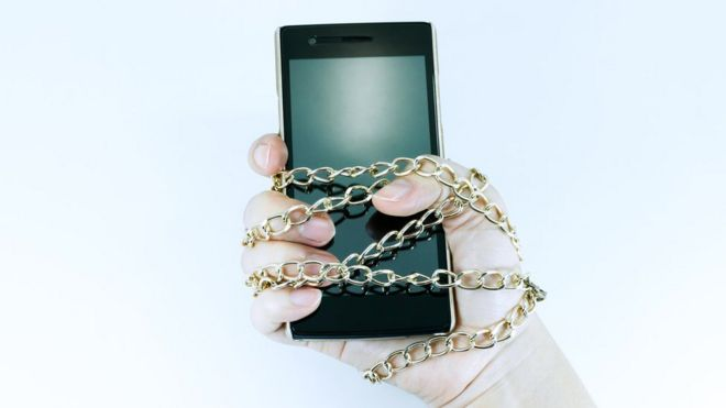 Mano encadenada a un celular