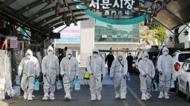 Market workers wearing protective gear spray disinfectant at a market in the south-eastern city of Daegu on February 23, 2020